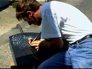 Jocelyn RENAUD, Graveur ornemaniste reconnu grave un motif décoratif sur un monument funéraire. Le geste doit être sûr car le graveur n'a pas de gomme.